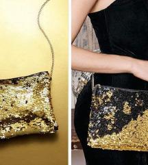 Mala zlatna torba koja prelazom ruke