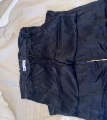 Dugacke crne pantalone sire se pri dnu